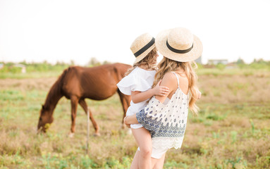 A beautiful young girl, with light curly hair in a straw hat with a little sister hugging and...