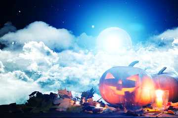Halloween pumpkin Jack-o'-lantern on wooden table with candles in a spooky night over moon and clouds