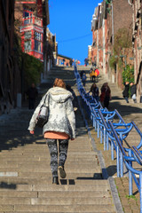 Beautiful young woman climbs the 374-step long staircase Montagne de Bueren, a popular landmark and tourist attraction in Liege, Belgium