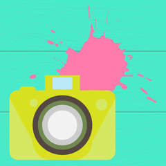 The old-fashioned color camera. Flat style. on a wooden background