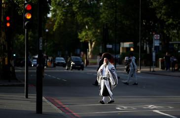 Jewish people walk around the Stamford Hill during Yom Kippur, in London