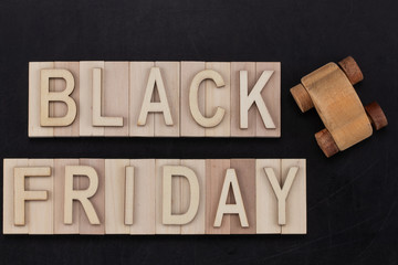 black Friday - text in wooden letters on blackBoard  with wooden car. Copy space