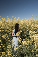 Girl in field of yellow flowers