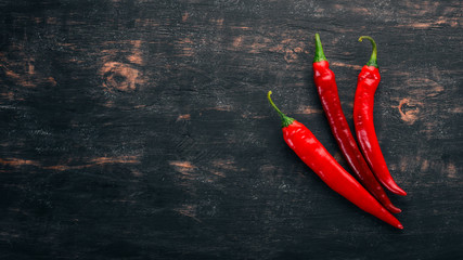 Chili red pepper. On a black wooden background. Free space for text. Top view.