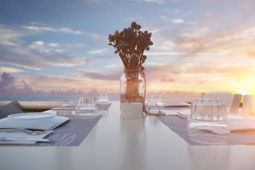 Portrait of a table of a restaurant with plates and glasses on, outside while a sunset.