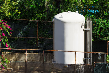 the plastic tank containing a water for supplying hotel visitors with comfortable conditions. the container standing outdoors under the sun near the plants and fence