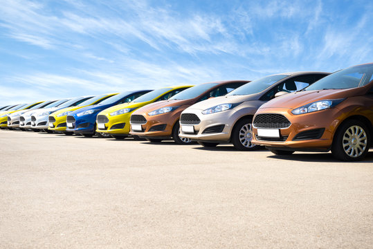 Vibrant new cars for sale stock lot row against blue sky at the sunrise