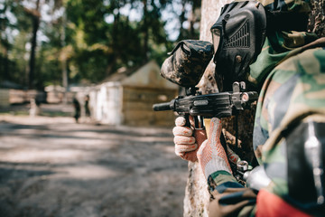 selective focus of paintball player in goggle mask and camouflage aiming by paintball gun outdoors