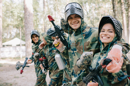 smiling young male paintballer embracing female teammate in camouflage with paintball gun outdoors