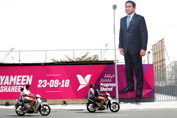 People ride motorcycles past an image of Maldives President Abdulla Yameen on a road ahead of the presidential election in Male