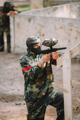 side view of confident male paintball player in goggle mask and camouflage aiming by paintball gun outdoors