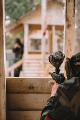 partial view of paintball player in camouflage uniform aiming by paintball gun from wooden tower outdoors