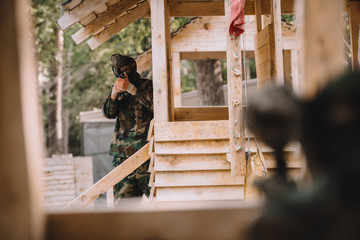 selective focus of male paintball player in goggle mask and camouflage aiming by paintball gun on wooden tower