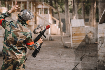 rear view of male paintball player in goggle mask and camouflage with paintball gun standing near net outdoors