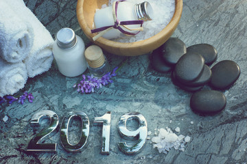 Set for spa treatments in 2019 on marble stone with figures, bath salt and towels and black stones...