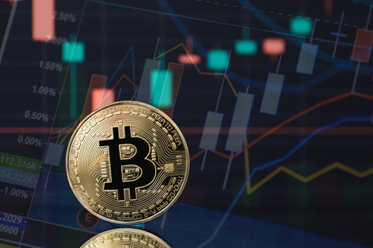 Bitcoin cryptocurrency coin token in gold with financial stock market charts in the background. Concept for digital currency trading and blockchain technology of the future.