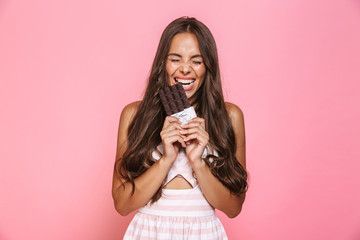 Photo of joyous woman 20s wearing dress smiling and eating chocolate bar, isolated over pink background