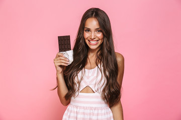 Photo of lovely woman 20s wearing dress smiling and eating chocolate bar, isolated over pink background