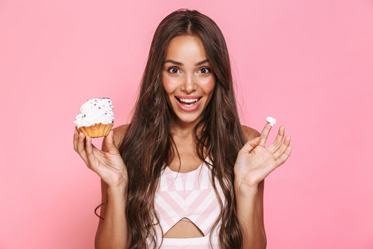 Photo of happy woman 20s wearing dress having fun while eating cupcake, isolated over pink background