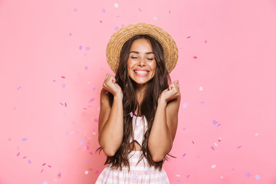 Photo of pretty woman 20s wearing straw hat laughing while standing under confetti, isolated over pink background