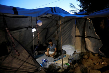 A migrant rests inside his tent at a makeshift camp next to the Moria camp for refugees and migrants on the island of Lesbos