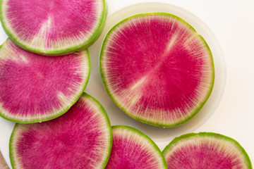 Close view of watermelon radish slices on a white plate, horizontal aspect