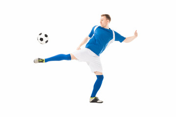 full length view of athletic young soccer player kicking ball isolated on white