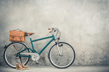 Retro bike with aged leather postman's bag and old sneakers front concrete wall background. Vintage style filtered photo