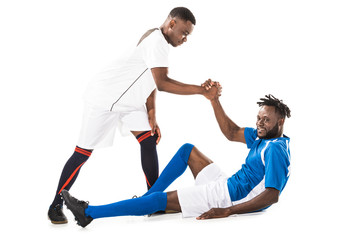 young african american sportsman helping soccer player lying isolated on white