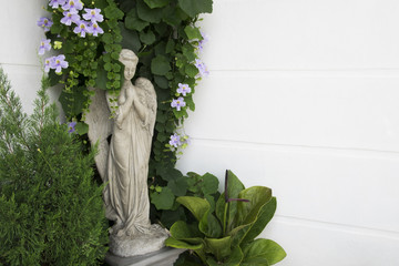 Cement angel statue with plant and flower decorations in the garden.