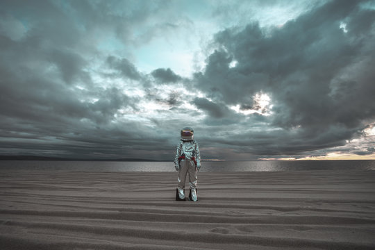 Spaceman standing alone at lake on nameless planet