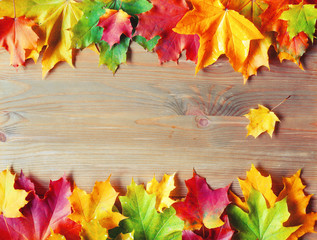 Autumn background. Maple colorful autumn leaves on the wooden background