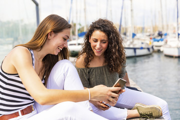 Two happy female friends looking at a smartphone at a marina