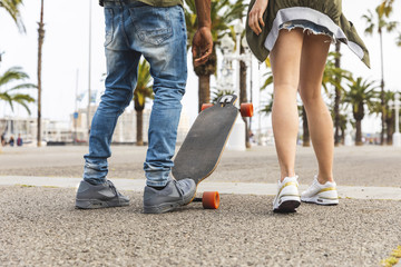 Spain, Barcelona, legs of multicultural young couple with longboard standing on promenade