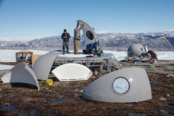 Oceanographer David Holland works with safety officer Brian Rougeux (R) and Febin Magar to assemble a fiberglass structure in the research camp above the Helheim glacier near Tasiilaq, Greenland