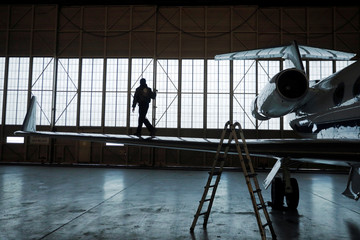 Airplane Mechanic, Angel Vazquez, walks on the wing of a NASA Gulfstream III during a pre-flight inspection of the aircraft before a flight to support the Oceans Melting Greenland (OMG) research mission at Keflavik International Airport, Iceland