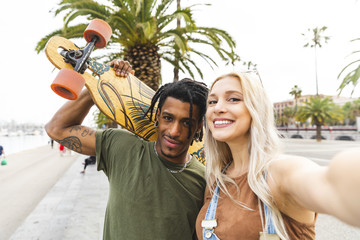 Spain, Barcelona, portrait of multicultural young couple taking selfie at promenade