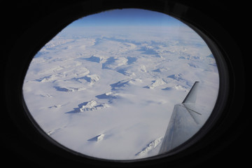 The Greenland ice sheet is shown out the window of a NASA Gulfstream III flight to support the Oceans Melting Greenland (OMG) research mission above the east coast of Greenland