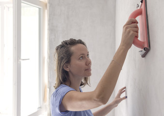 Young woman working with rubbing board on plaster