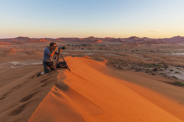 Photographer on sand dune at sunrise