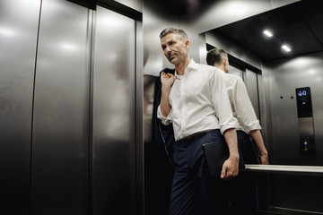 Businessman in elevator holding laptop
