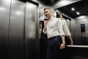 Businessman in elevator holding laptop