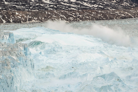 Ocean water is pushed up by the bottom of a pinnacle iceberg as it falls back during a large calving event at the Helheim glacier near Tasiilaq, Greenland