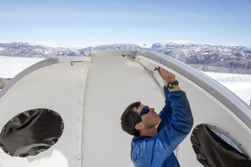 Safety officer Brian Rougeux works to build a semi-permanent structure at the research camp above the Helheim glacier near Tasiilaq, Greenland