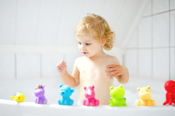 Adorable cute little toddler girl taking bath in bathtub. Happy healthy baby child playing with rubber gum toys and having fun. Washing, cleaning, hygiene for children.