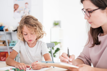 Child drawing pictures during meeting with therapist for orphan