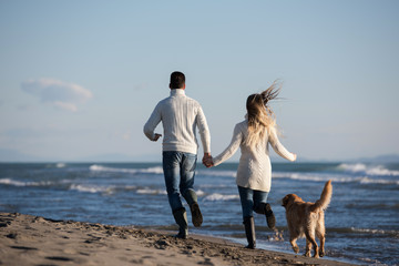 couple with dog having fun on beach on autmun day