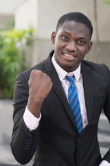 confident winning african businessman; portrait of successful confident african or black business man, manager, business executive winner being happy with success; young adult african man model