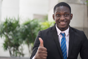 african businessman giving thumb up; portrait of successful confident african business man showing success thumb up gesture for winner, successful business deal; young adult african man model
