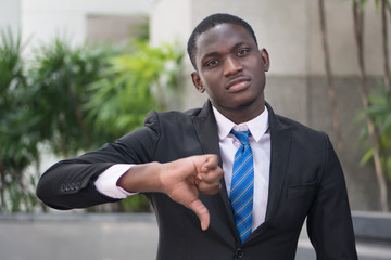 african businessman giving thumb down; portrait of upset angry african business man showing failed thumb down gesture for loser, profit lost, failed business deal; young adult african man model